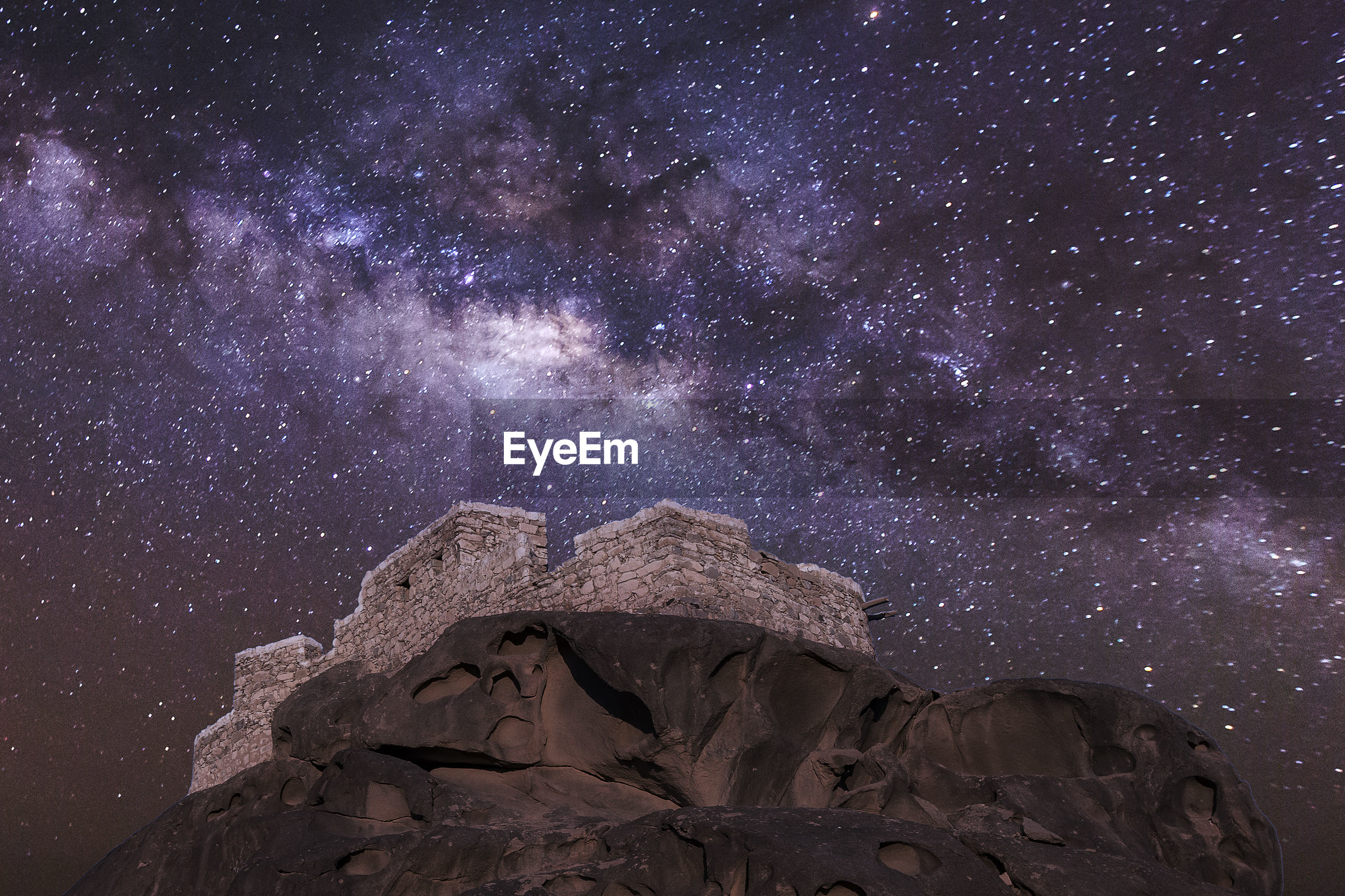 Low angle view of castle on mountain against star field
