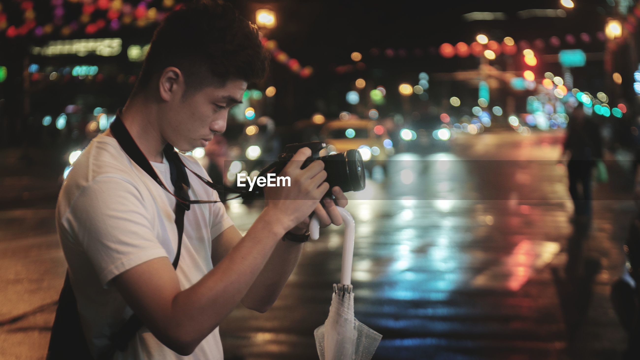Side view of young man photographing in city at night