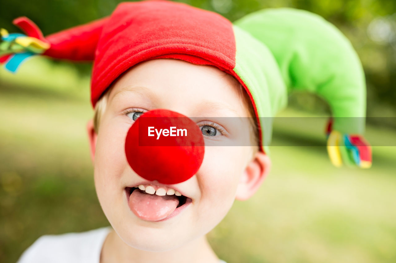 Close-up of playful boy wearing clown nose and hat in park