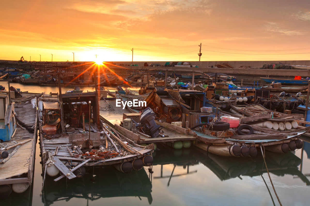 sunset, sky, water, sun, nature, cloud - sky, nautical vessel, transportation, mode of transportation, orange color, moored, no people, sunlight, outdoors, architecture, industry, harbor, sunbeam, built structure, sailboat, fishing industry, marina