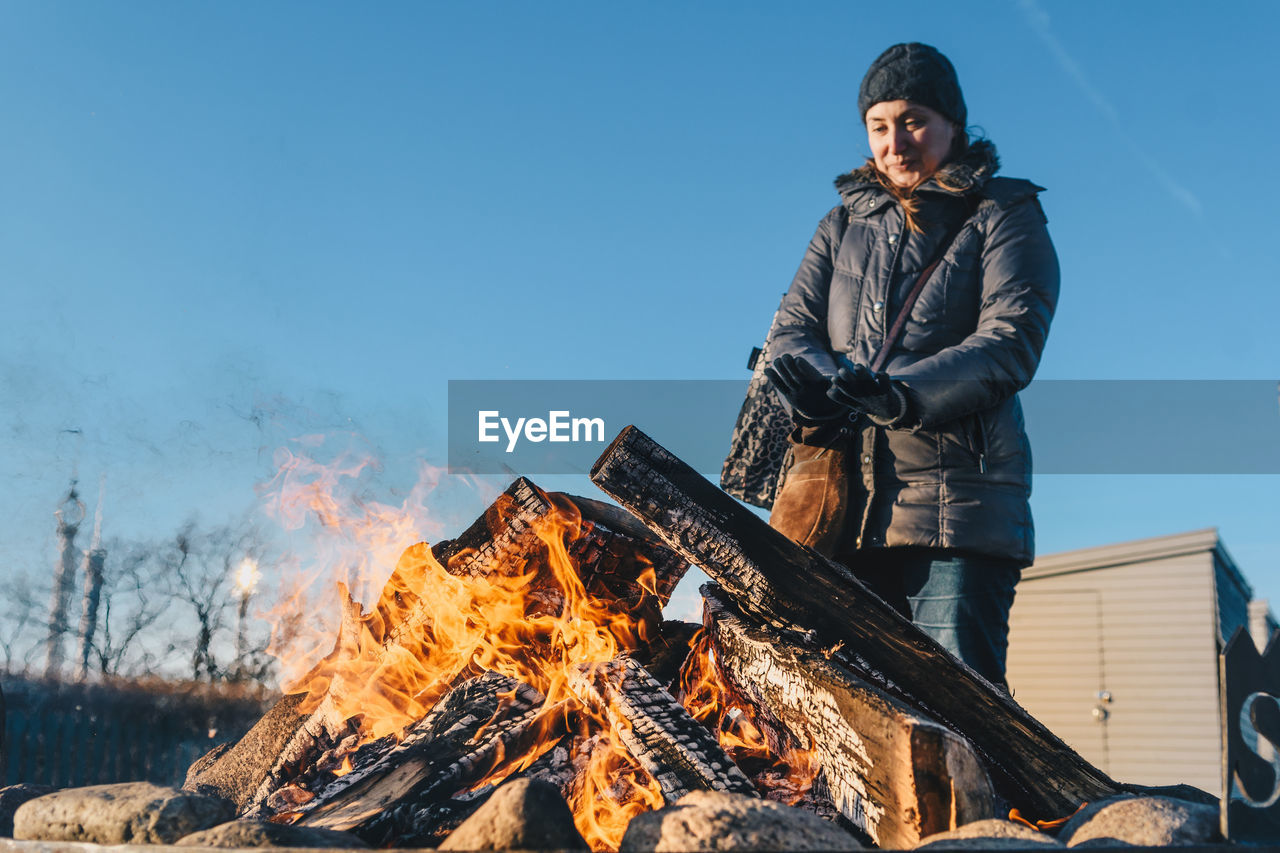 Low Angle View Of Woman Standing By Bonfire Against Blue Sky