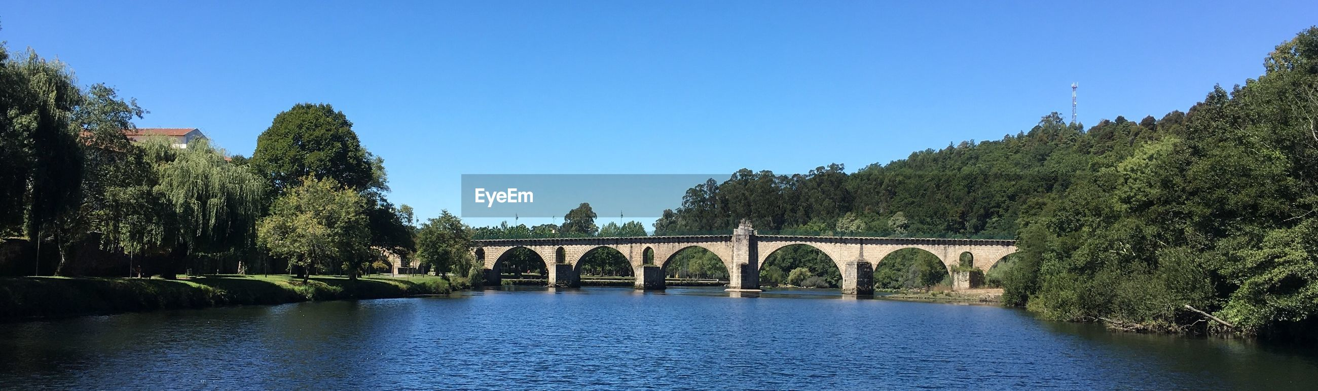 tree, clear sky, bridge - man made structure, arch, built structure, river, architecture, day, tranquil scene, blue, water, nature, no people, outdoors, tranquility, beauty in nature, waterfront, scenics, growth, sky, forest, mountain