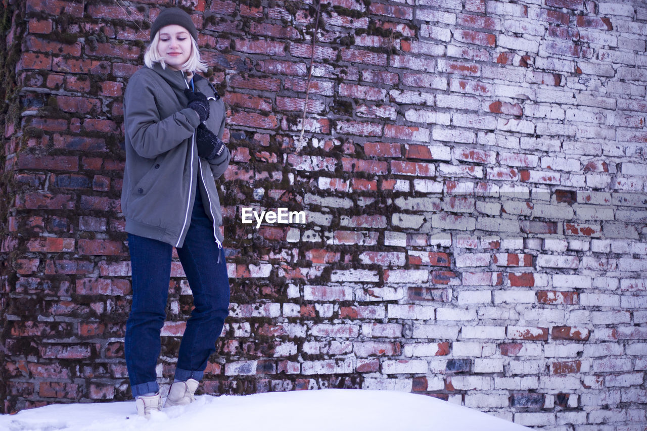 Young woman looking away standing against brick wall during winter