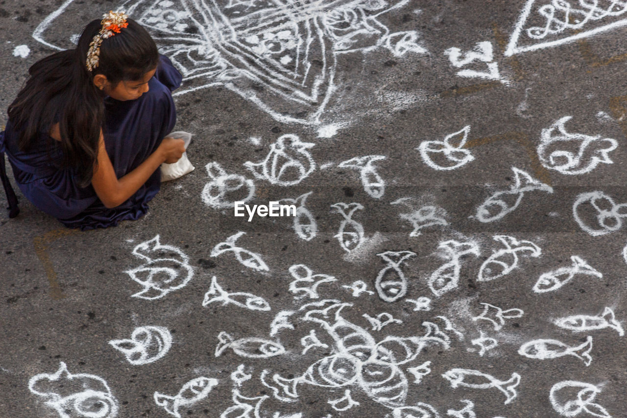 creativity, drawing - activity, chalk drawing, one person, doodle, sketch, casual clothing, people, sidewalk, high angle view, childhood, inspiration, real people, full length, children only, outdoors, child, young adult, day, blackboard, adult, hopscotch