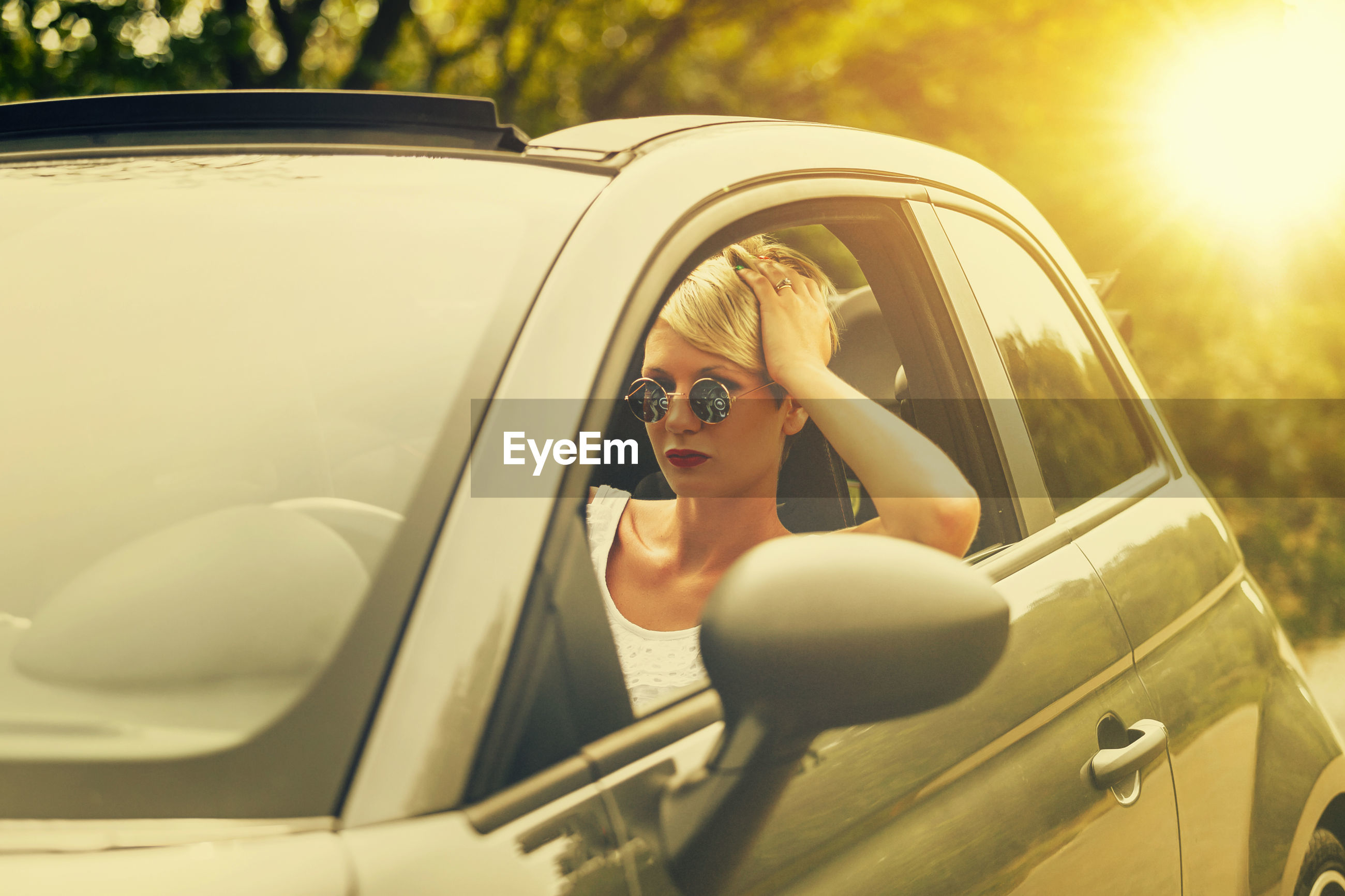 Portrait of woman wearing sunglasses sitting in car