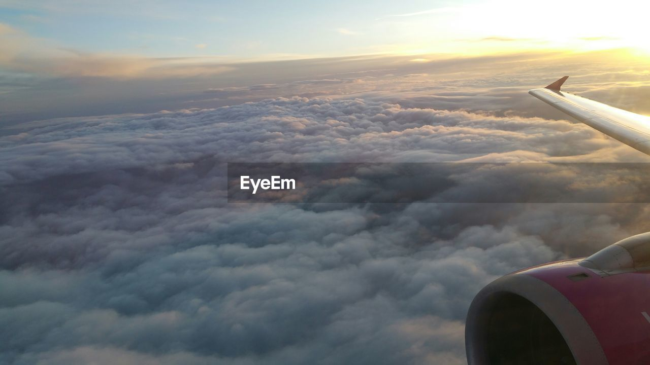 Cropped Image Of Airplane Wing Above Cloudy Sky