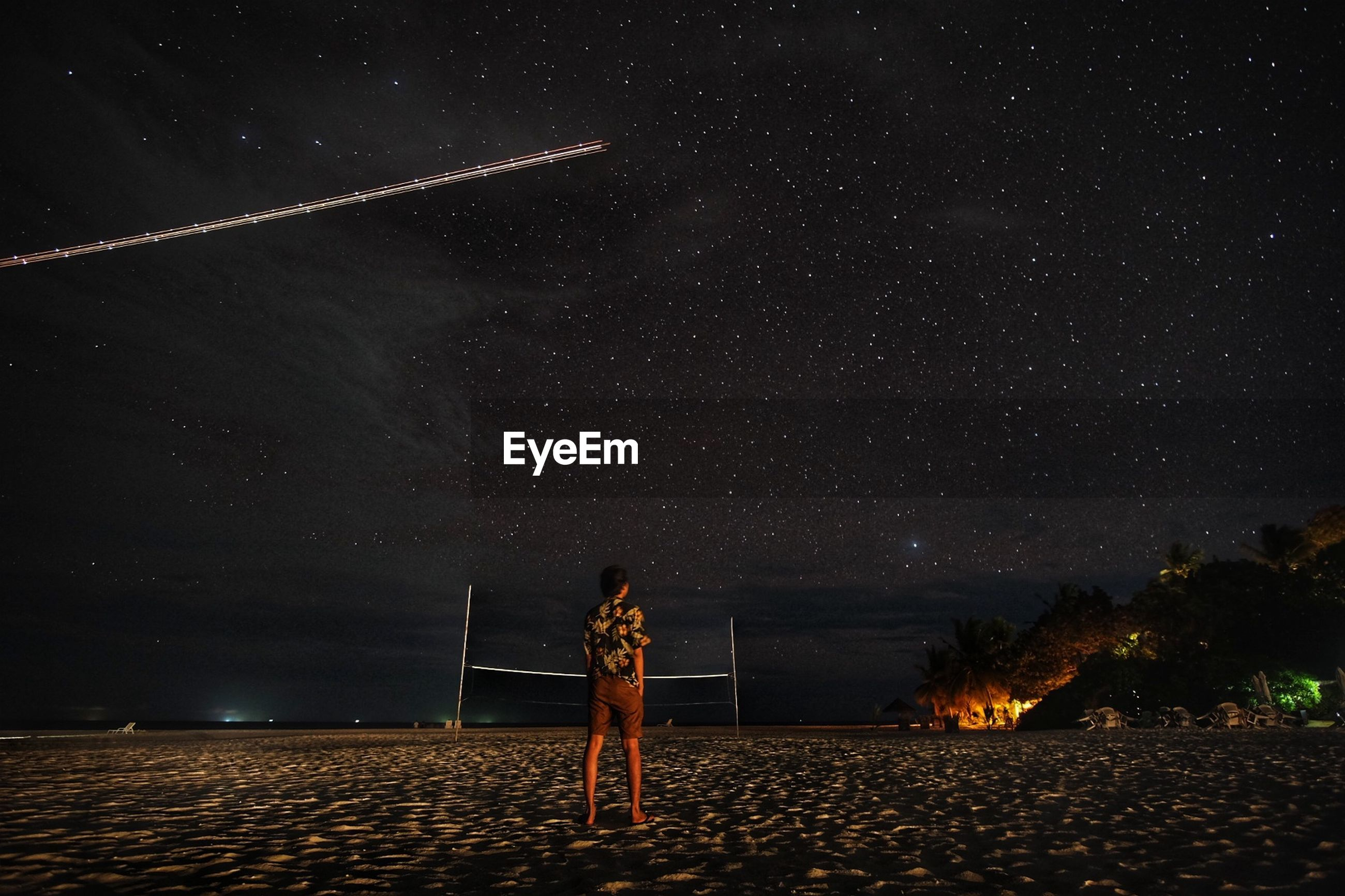 Rear view of man standing on field against star field at night