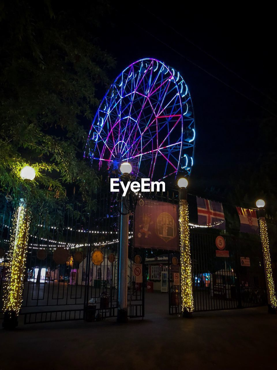 amusement park, night, amusement park ride, architecture, illuminated, built structure, ferris wheel, arts culture and entertainment, tree, no people, multi colored, low angle view, building exterior, sky, nature, plant, outdoors, circle, shape, dusk, fairground, nightlife