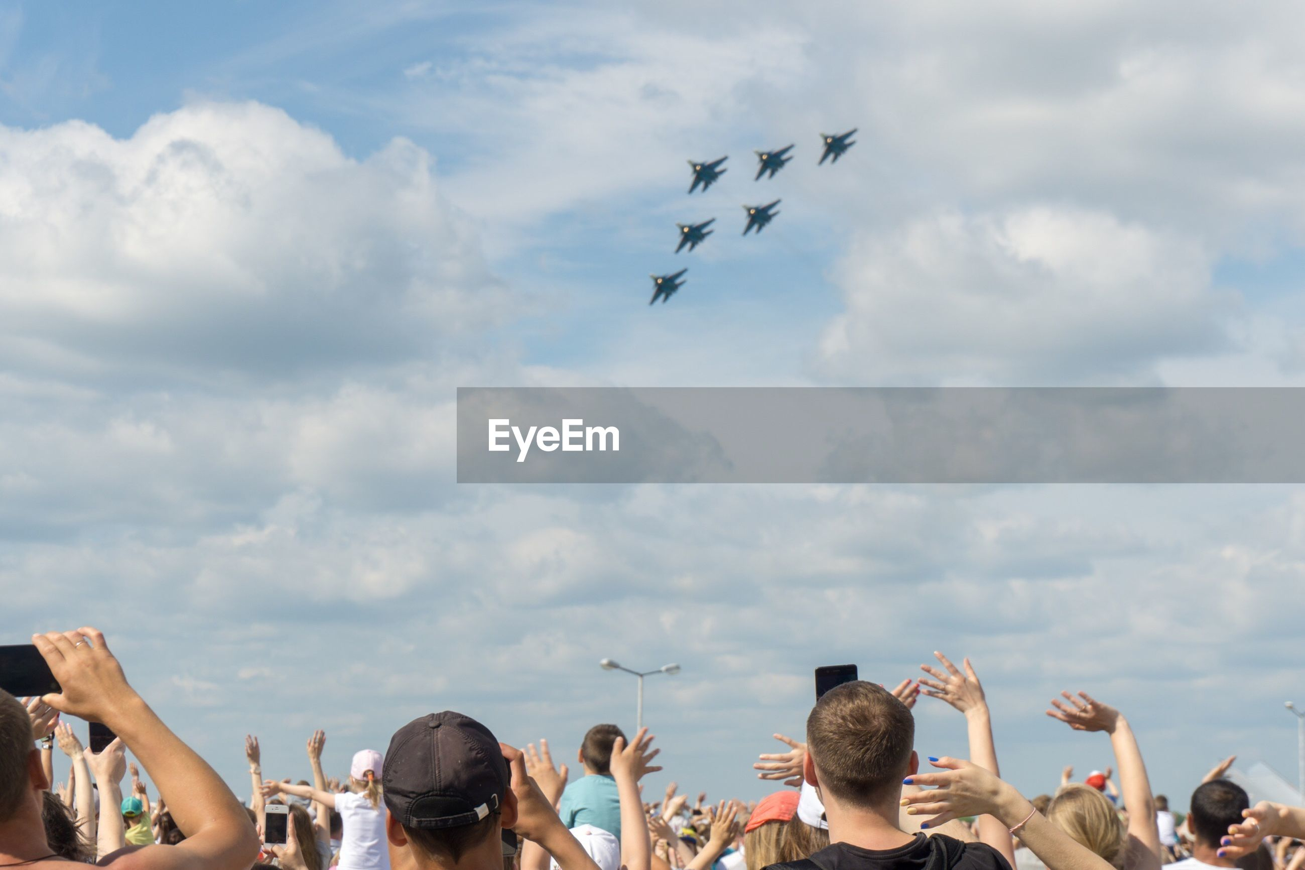 Low angle view of people watching airshow against sky