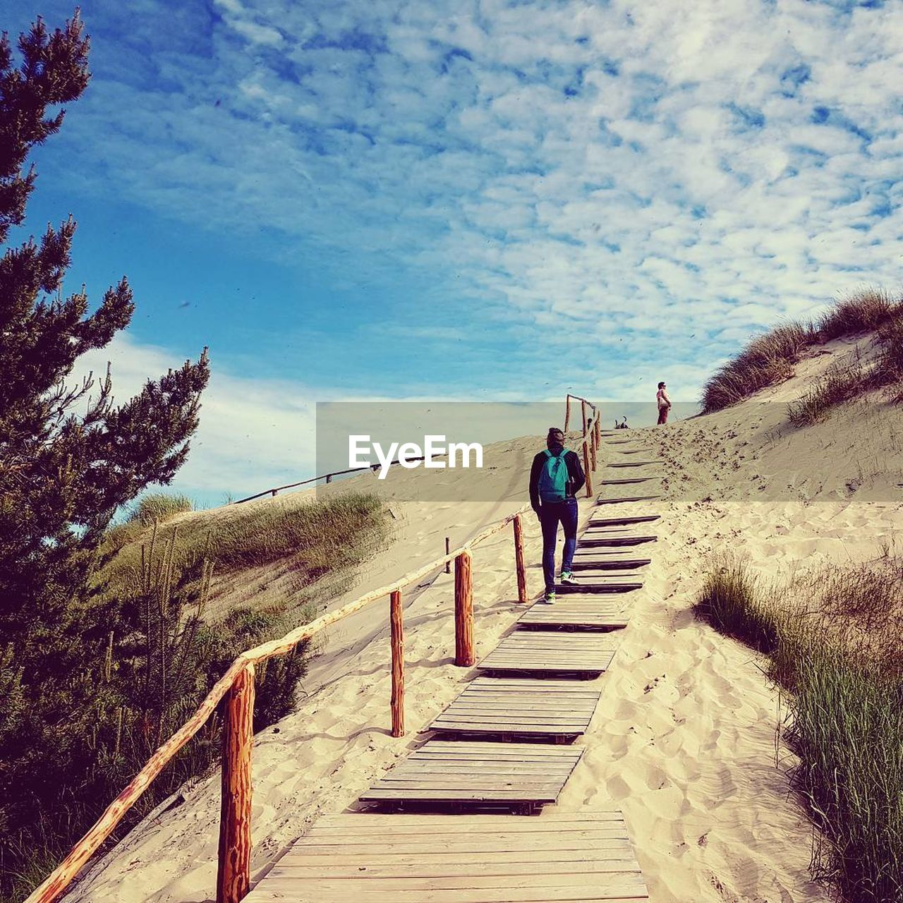 walking, full length, rear view, day, sand, nature, real people, sky, outdoors, the way forward, one person, steps, adventure, scenics, beauty in nature, vacations, sunlight, men, cloud - sky, lifestyles, tranquility, landscape, sand dune, mountain, one man only, adult, people