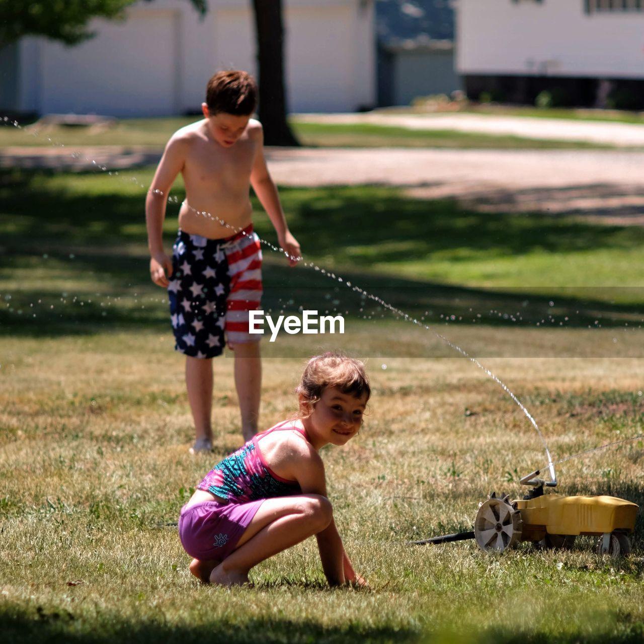 Water spraying on shirtless boy with sister in yard
