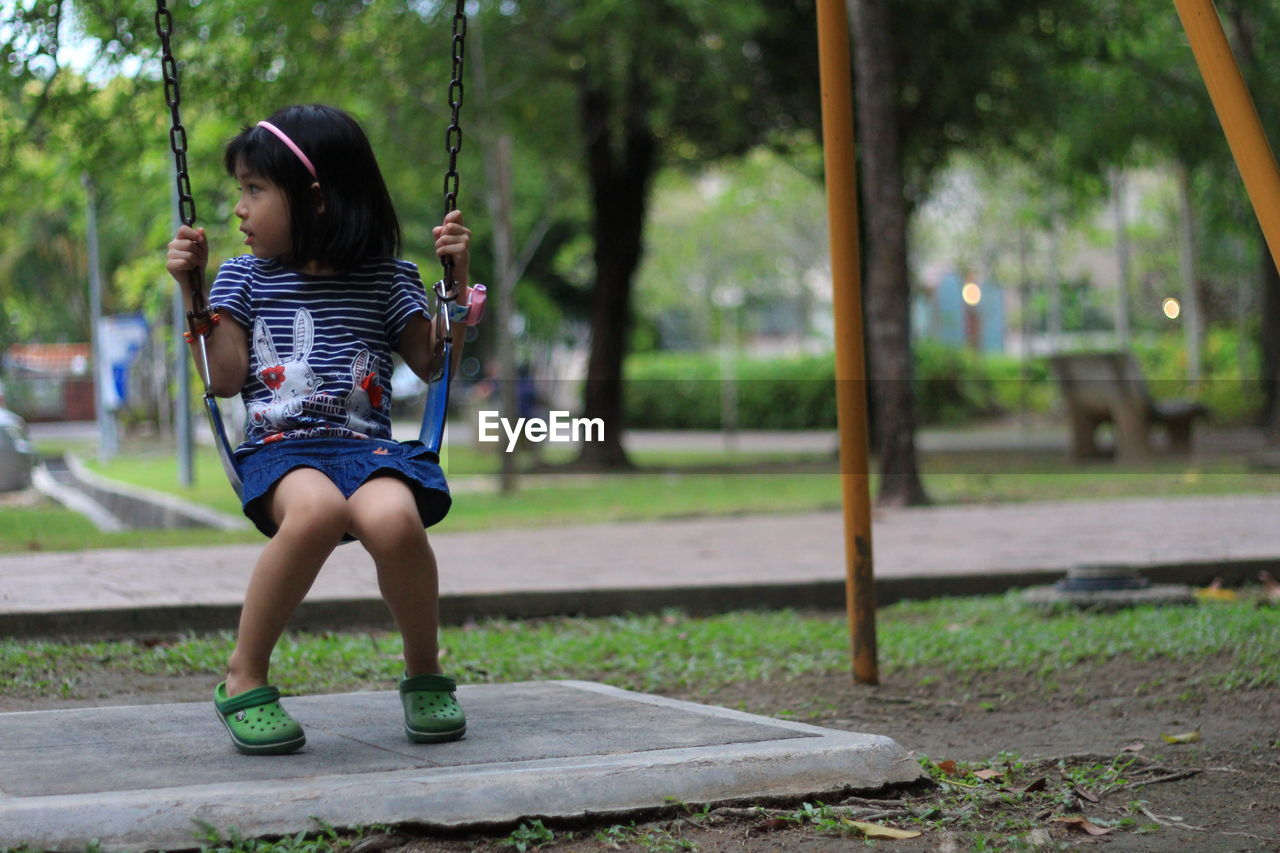 real people, childhood, leisure activity, one person, park - man made space, outdoors, casual clothing, full length, focus on foreground, lifestyles, day, tree, girls, nature, young adult