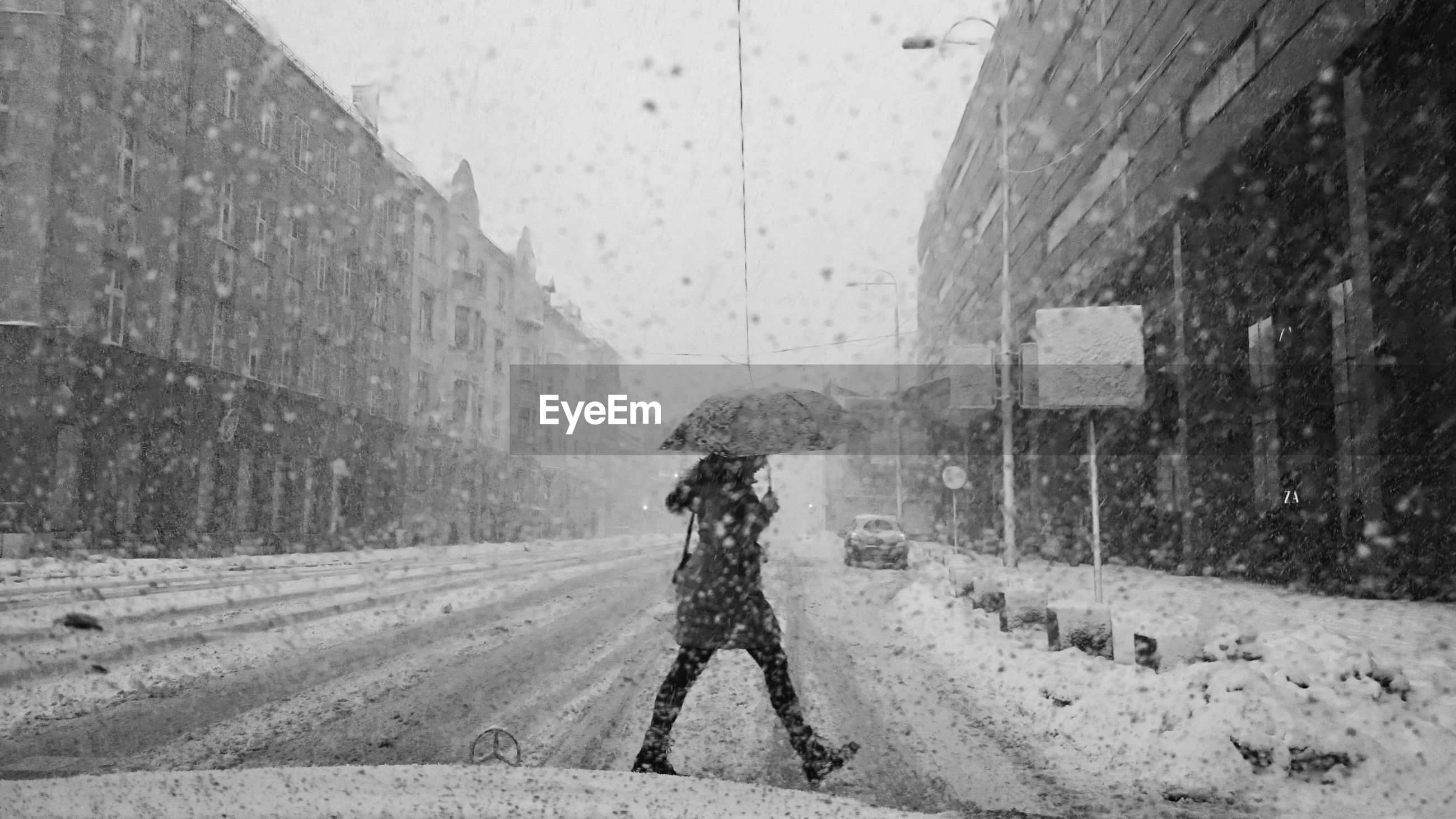 Side view of mid adult woman walking on road during snowfall seen through windshield
