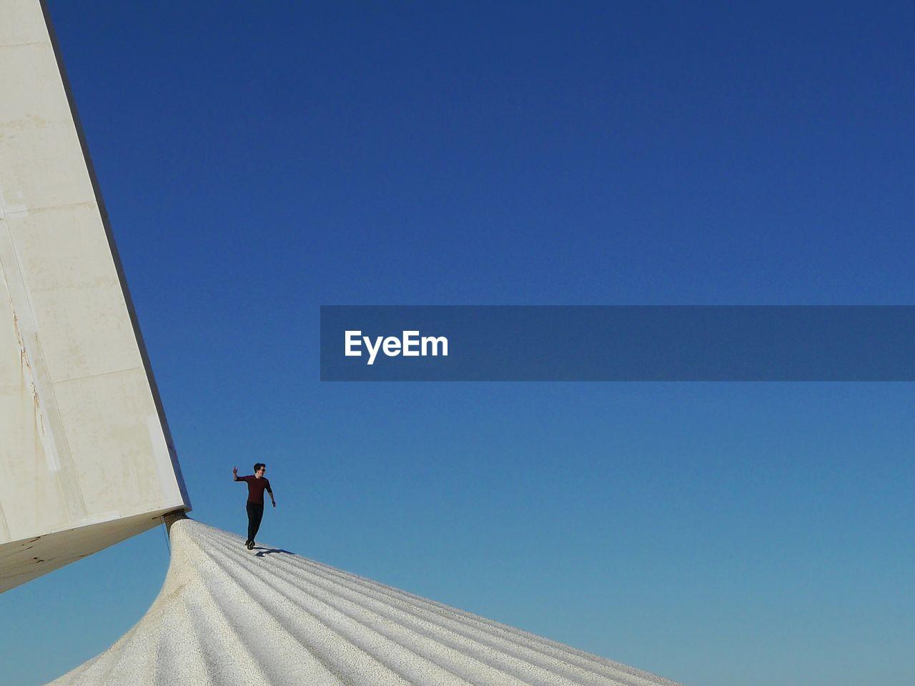Full Length Of Man Against Clear Blue Sky