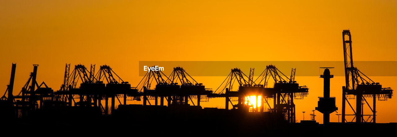 Silhouette cranes against clear sky during sunset