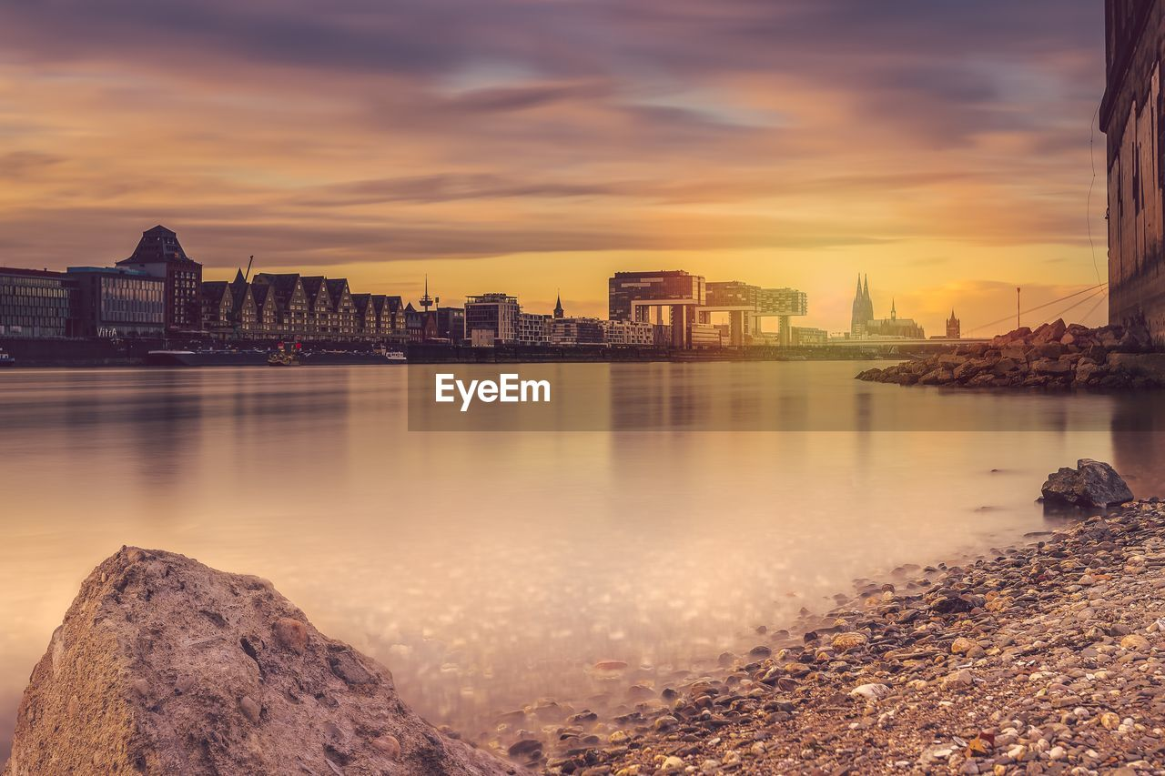 building exterior, architecture, built structure, water, sky, cloud - sky, city, building, sunset, nature, reflection, waterfront, no people, urban skyline, river, office building exterior, rock, outdoors, cityscape, skyscraper, bay