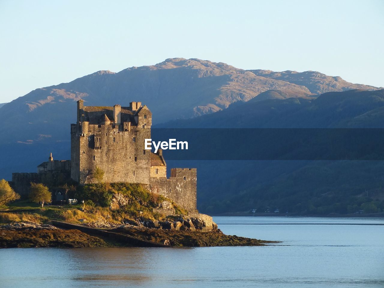 Eilean Donan Castle By River Against Mountains