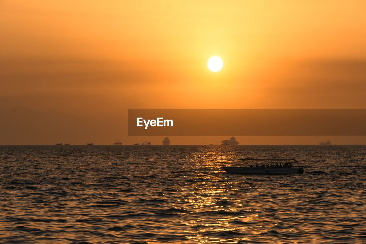 sky, water, sunset, beauty in nature, sea, sun, scenics - nature, orange color, nautical vessel, transportation, waterfront, mode of transportation, idyllic, tranquil scene, nature, sunlight, tranquility, horizon over water, silhouette, no people, outdoors