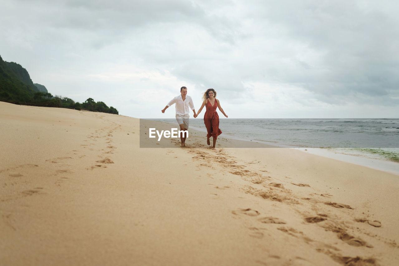 Women standing on beach against sky