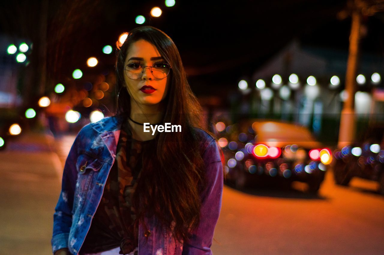 Portrait of young woman wearing eyeglasses on illuminated street at night