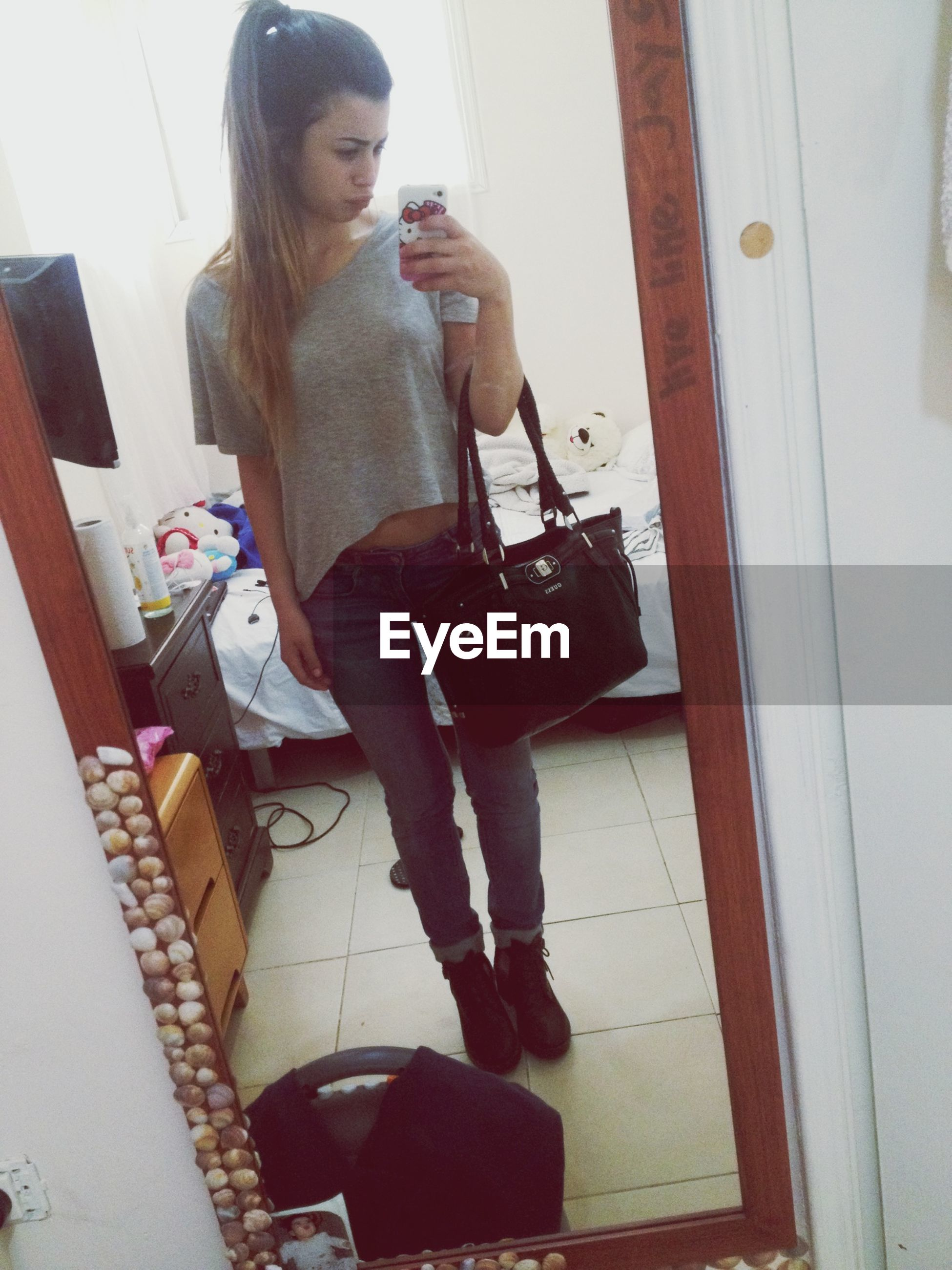 indoors, young adult, lifestyles, person, casual clothing, young women, leisure activity, full length, front view, home interior, standing, mirror, holding, three quarter length, technology, wireless technology, sitting, wall - building feature
