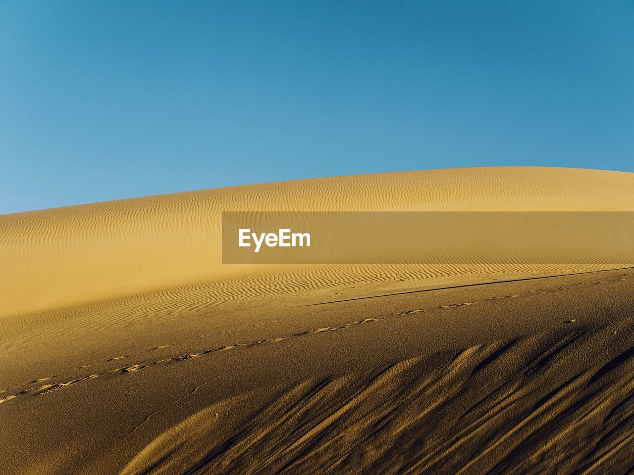 View of sand dunes against clear sky