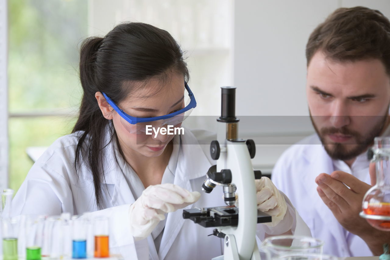 Scientists with microscope experimenting in laboratory