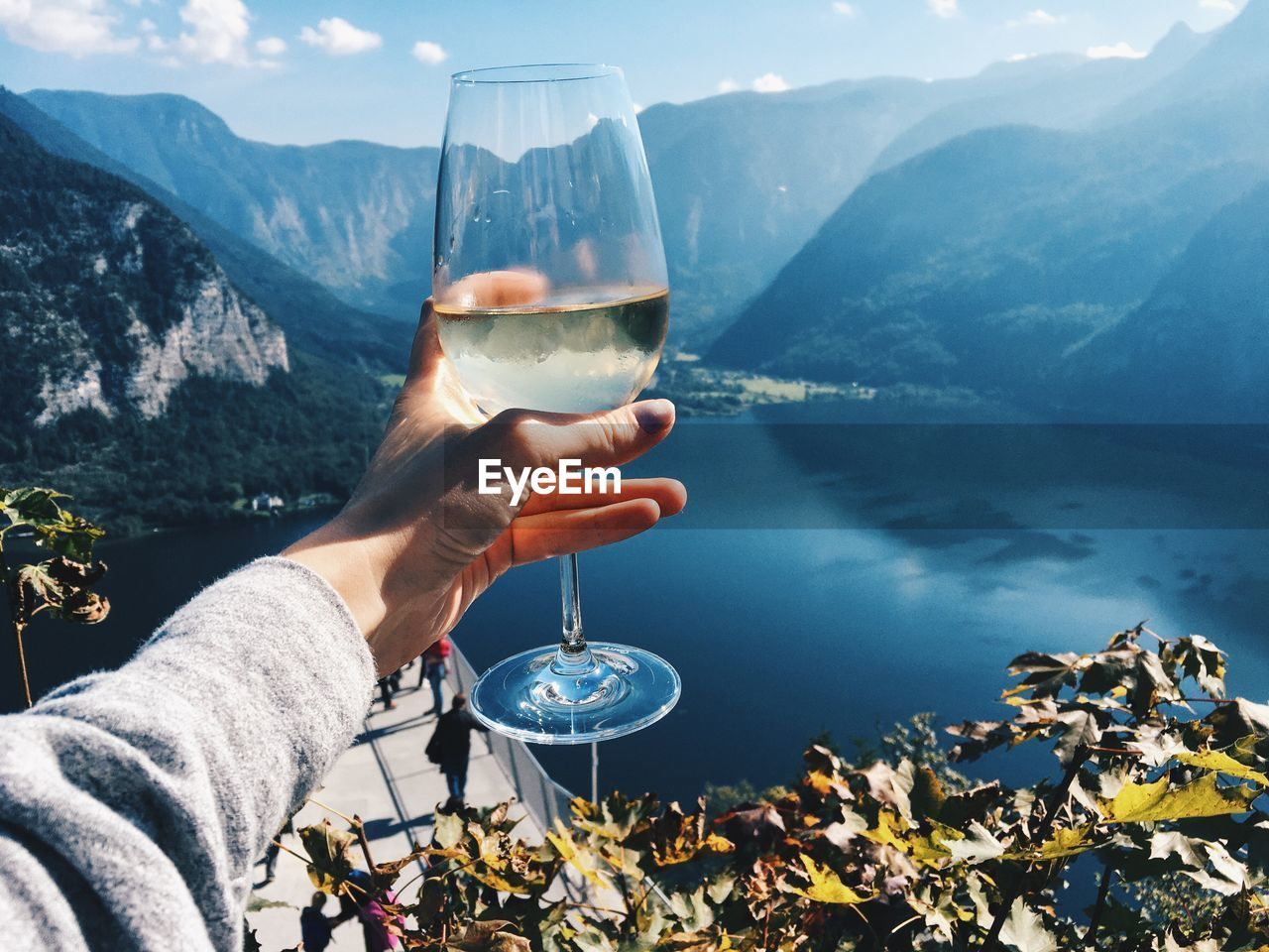 Close-up of human hand holding alcoholic drink by lake against mountains