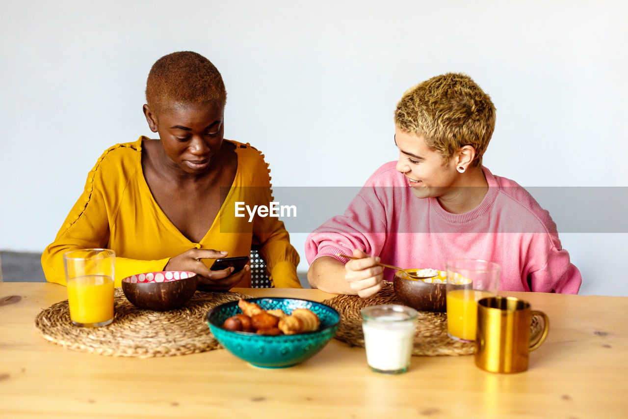 PEOPLE LOOKING AWAY WHILE SITTING AT TABLE