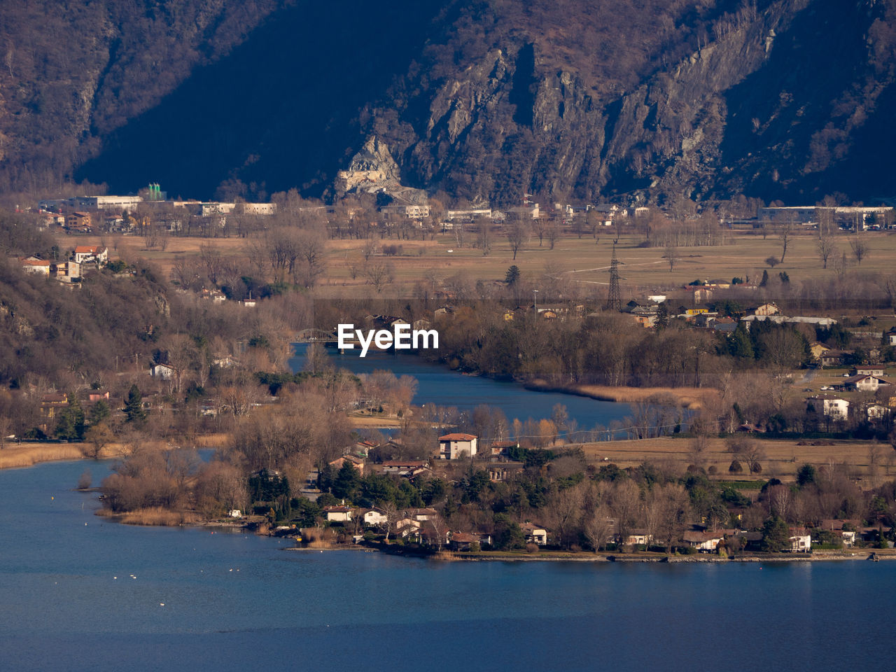 Scenic View Of Lake By City Against Mountain
