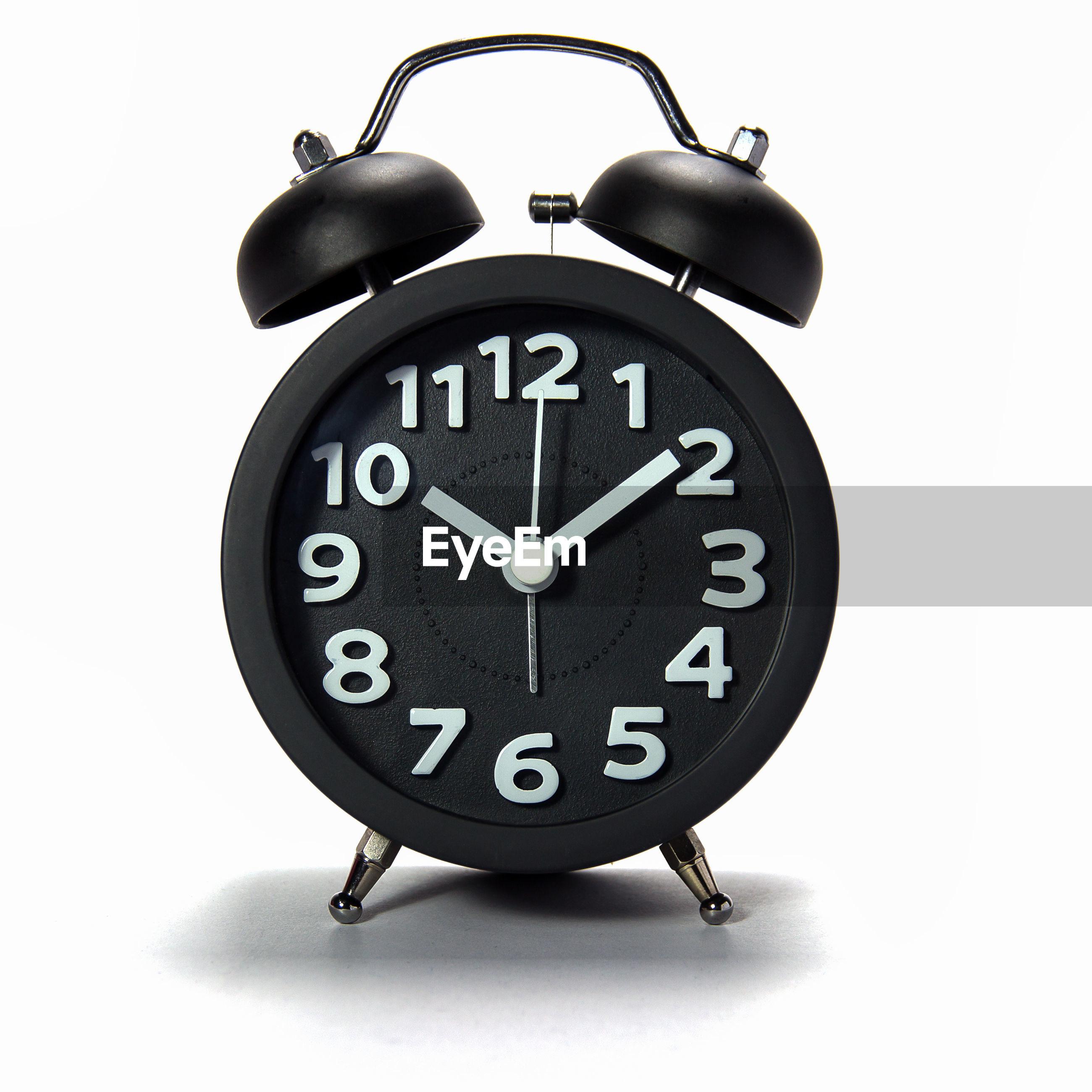 Close-up of alarm clock against white background