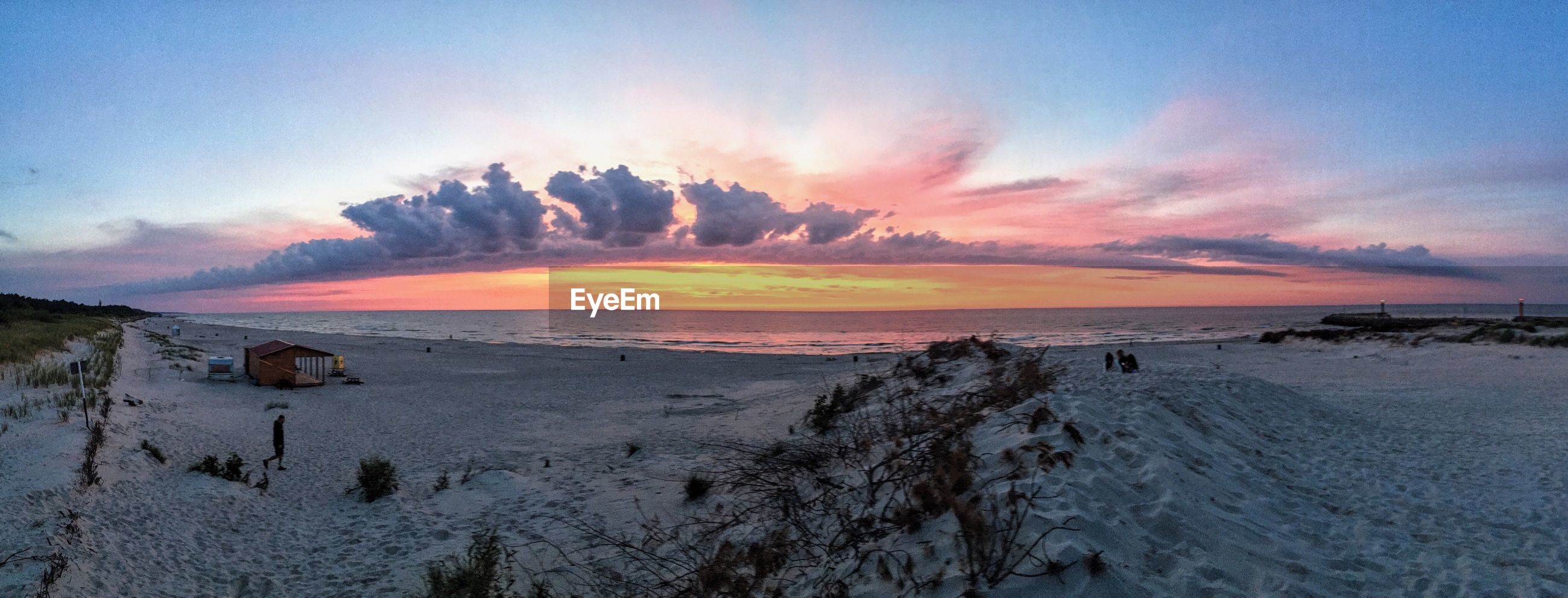 PANORAMIC VIEW OF BEACH AGAINST ROMANTIC SKY AT SUNSET