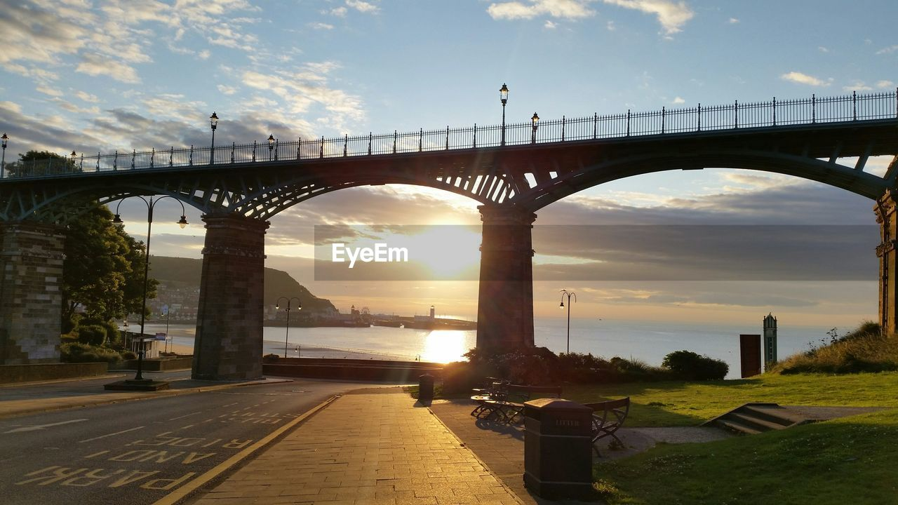Low angle view of bridge over street leading towards sea during sunset