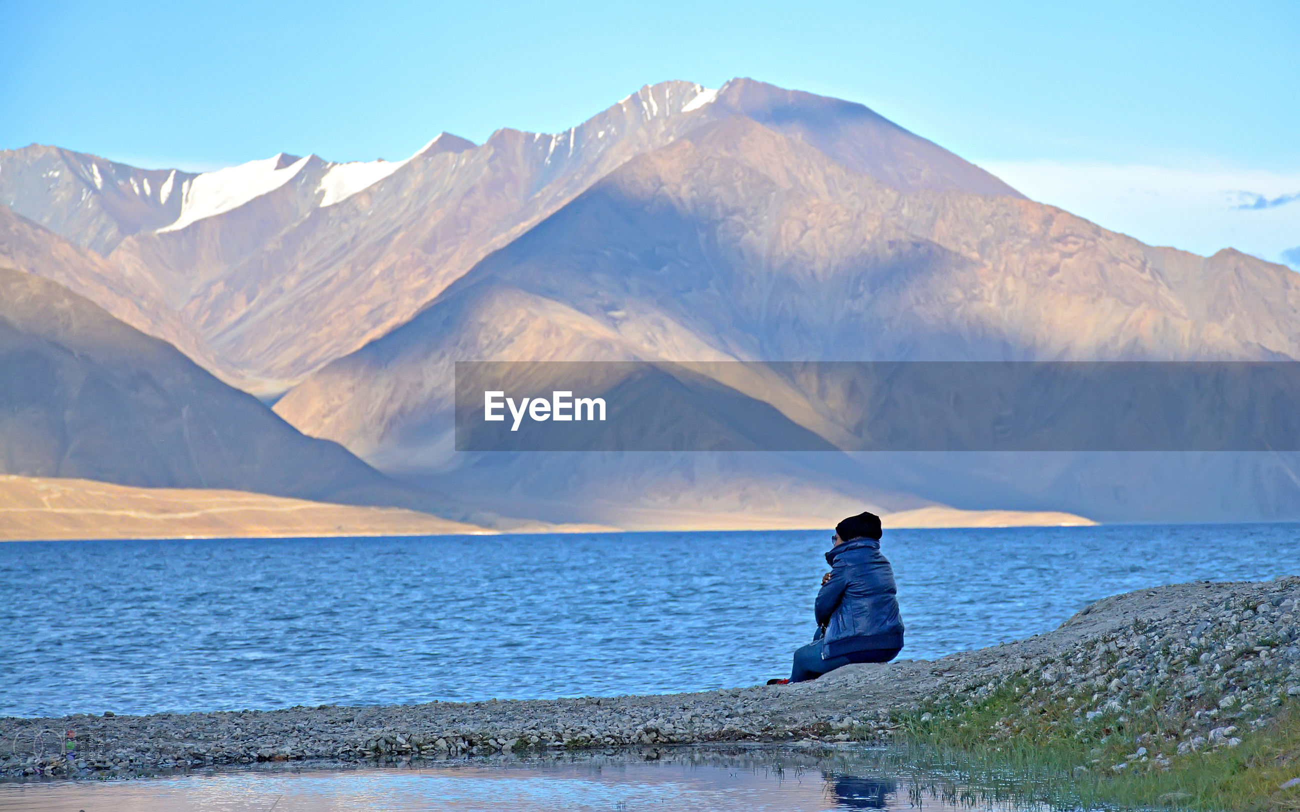 Side view of woman sitting by lake against mountains