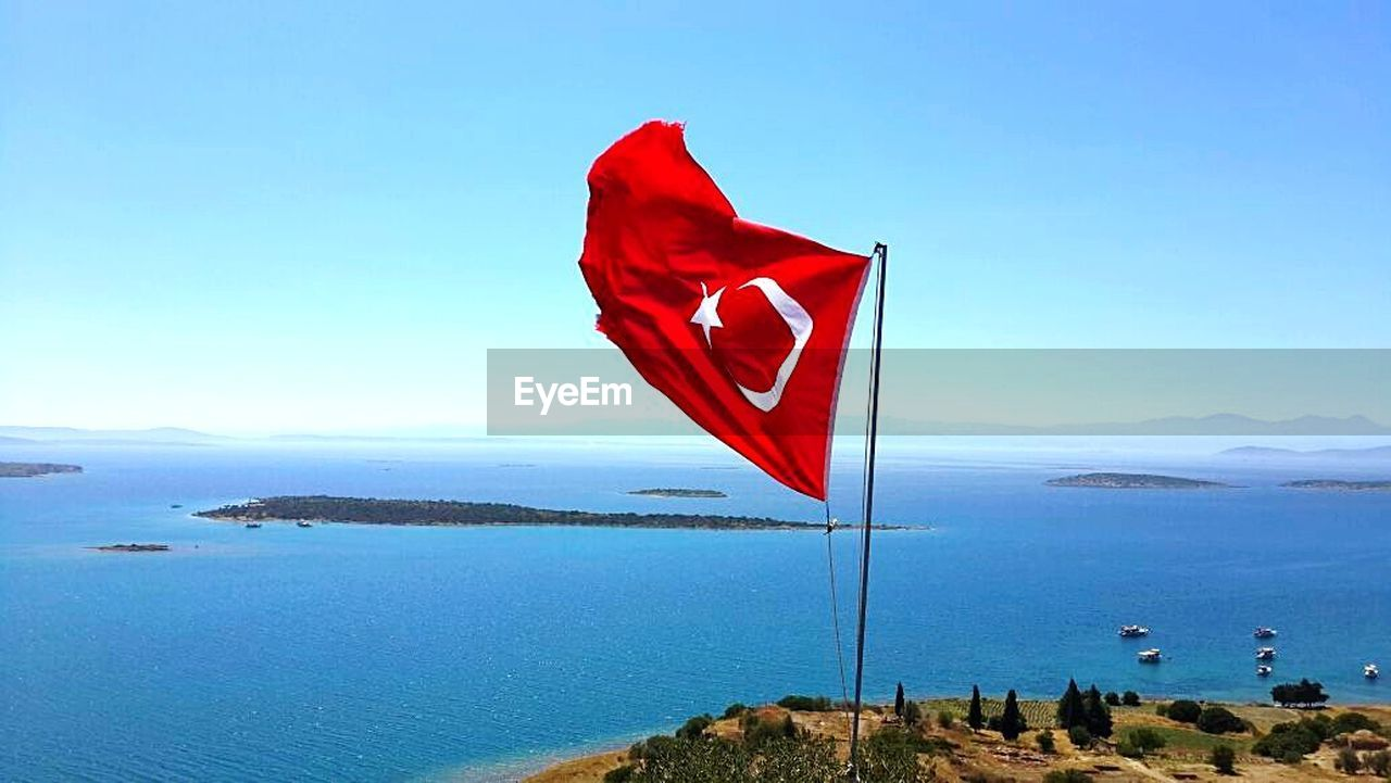 flag, red, patriotism, blue, water, nature, sea, mountain, flying, sky, day, scenics, beauty in nature, outdoors, no people, landscape, clear sky