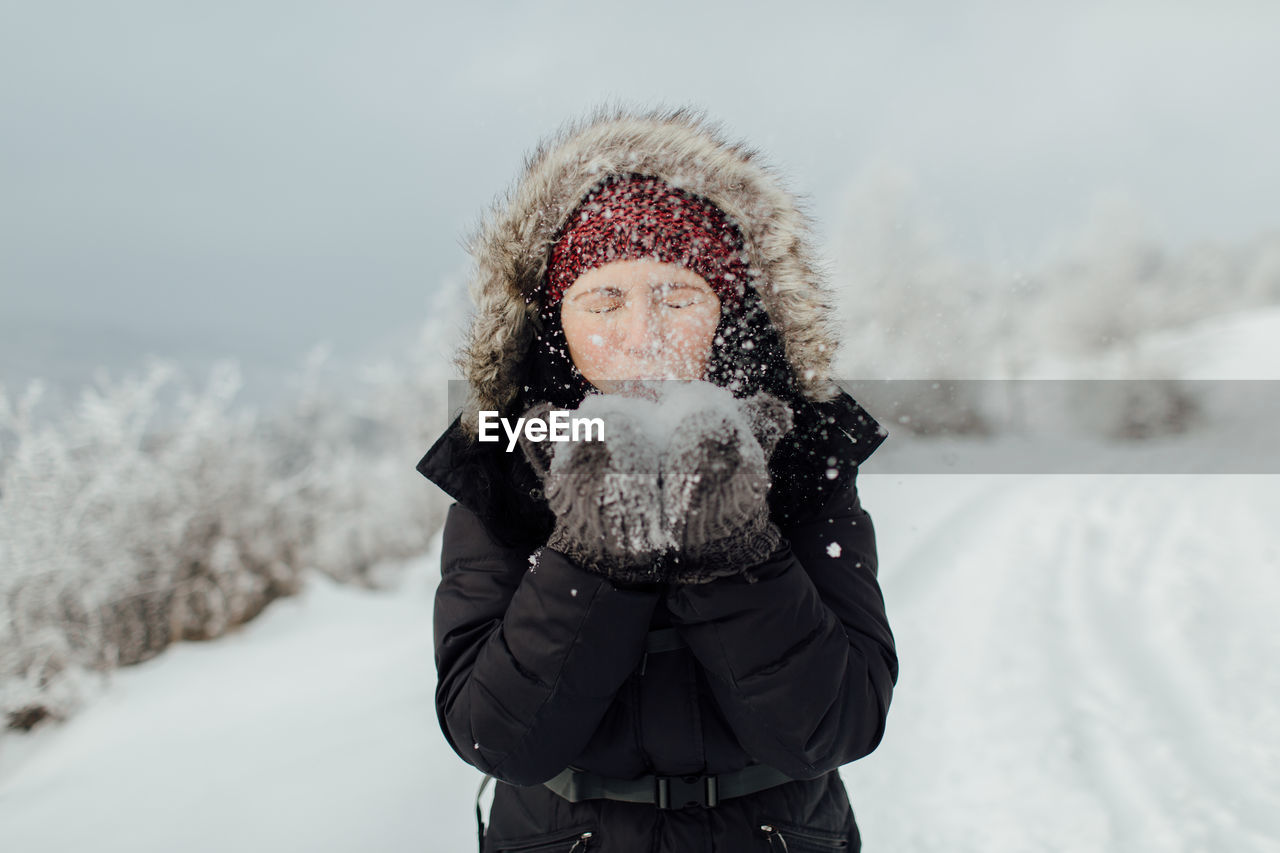 Playful Woman Blowing Snow From Hands While Standing On Mountain