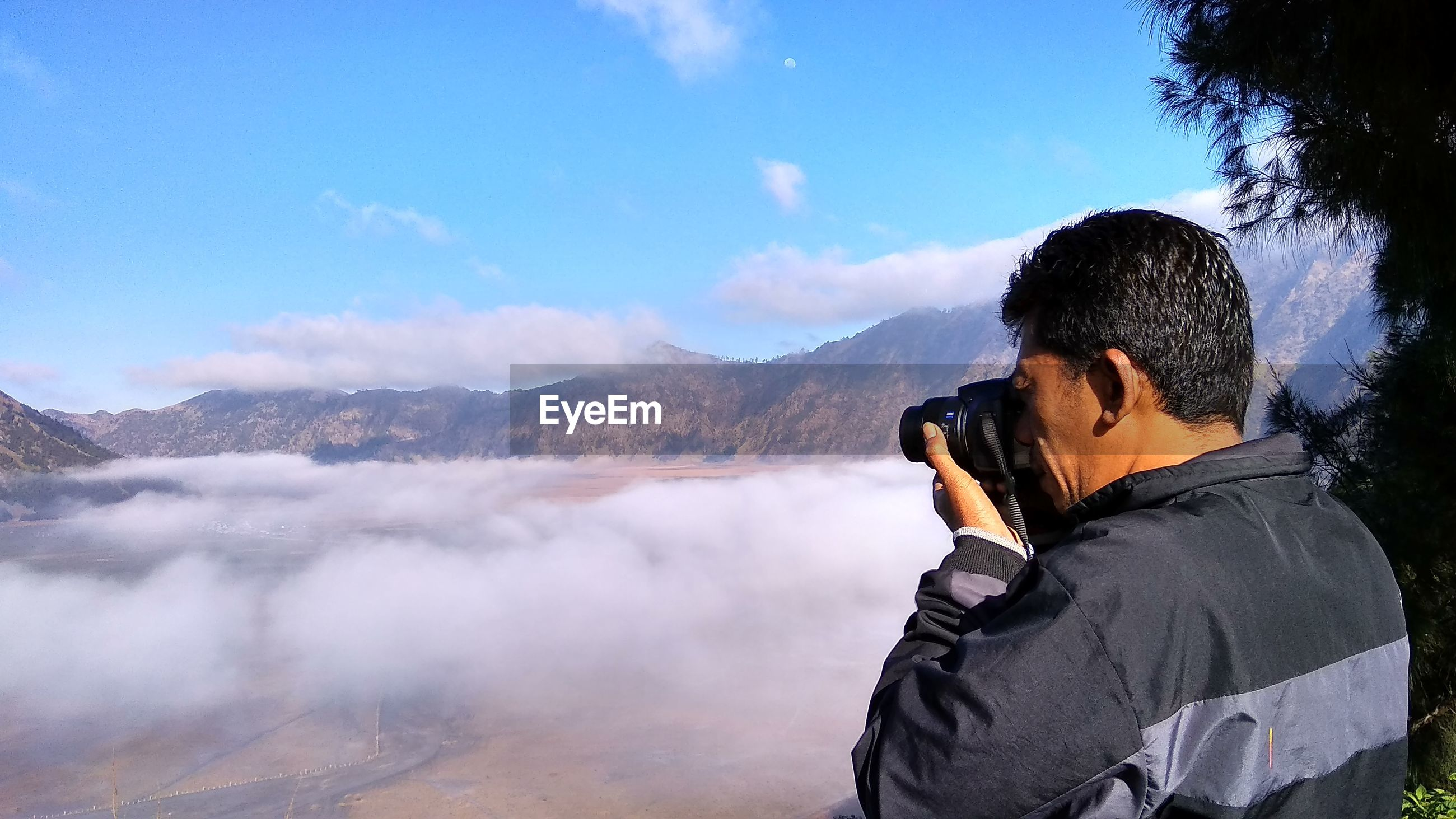 man photographing foggy landscape against mountain