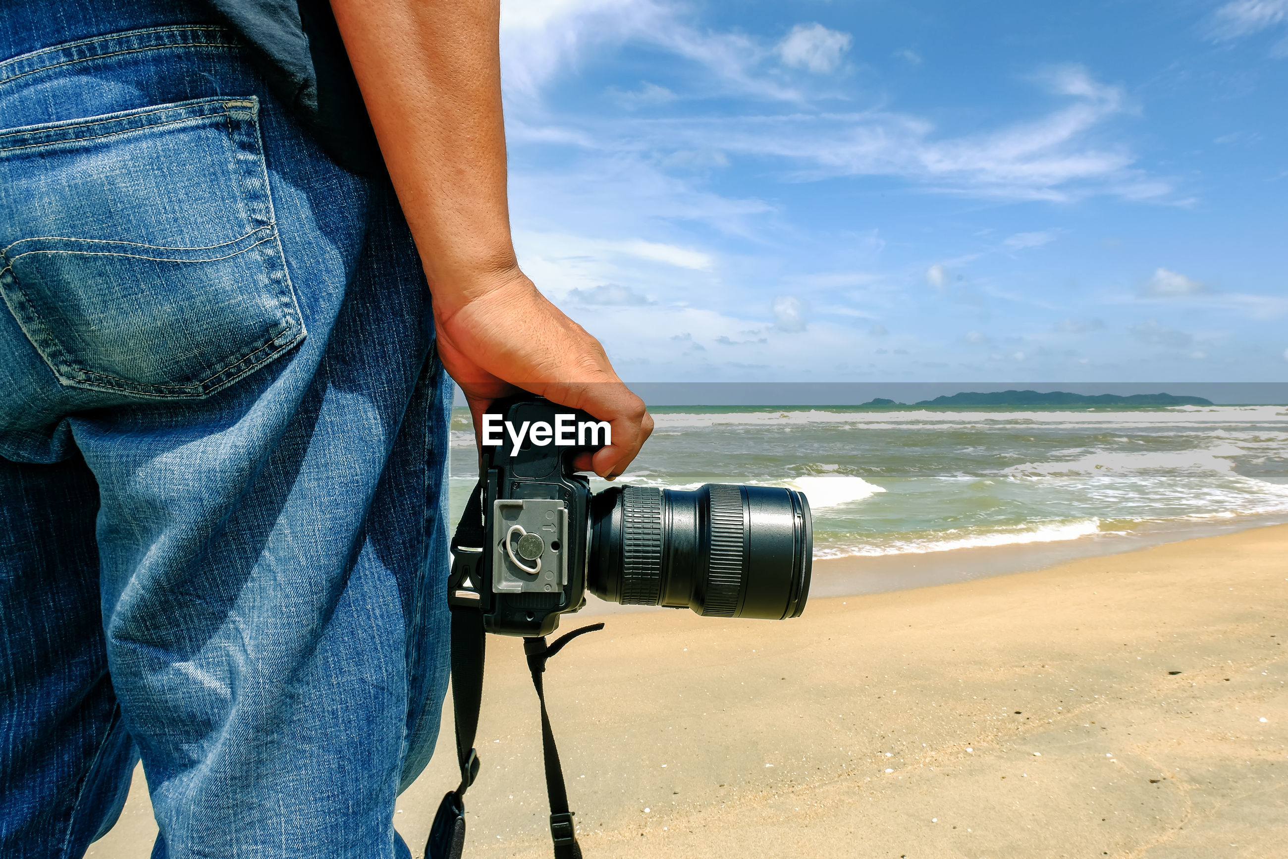 Man holding camera on beach