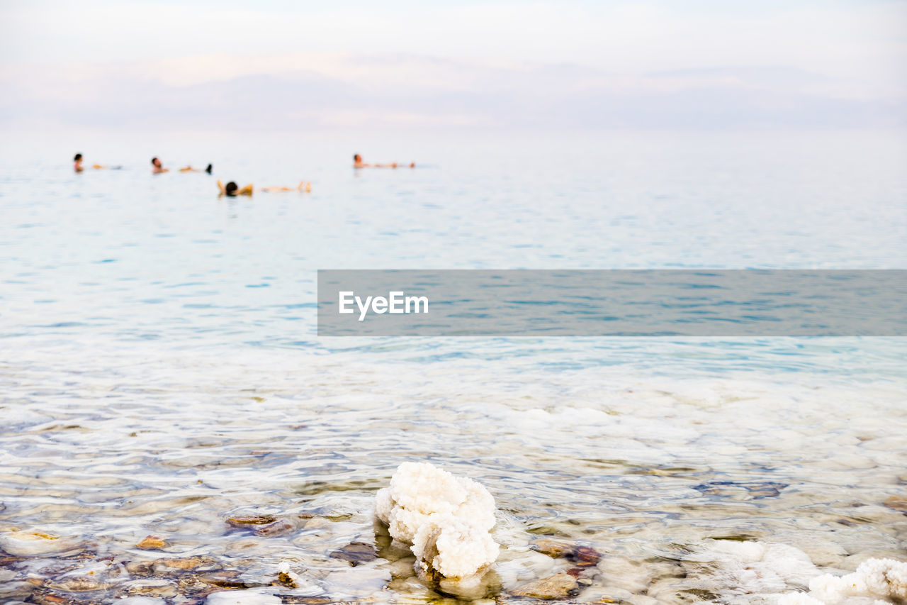 water, sea, sky, beach, land, nature, beauty in nature, tranquility, scenics - nature, solid, tranquil scene, incidental people, rock, vacations, day, horizon, trip, cloud - sky, focus on foreground, horizon over water, outdoors