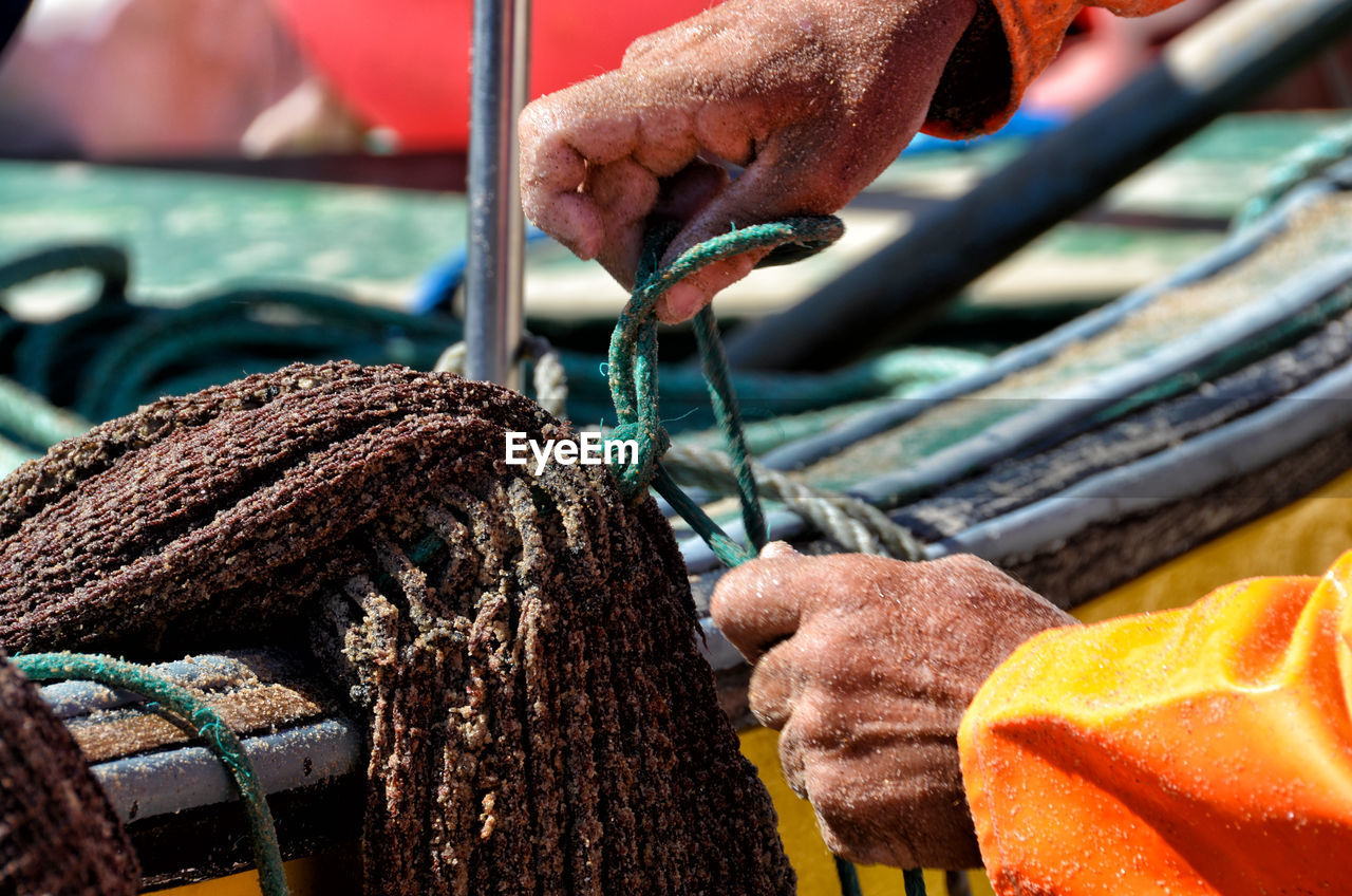 Cropped hands tying rope on boat