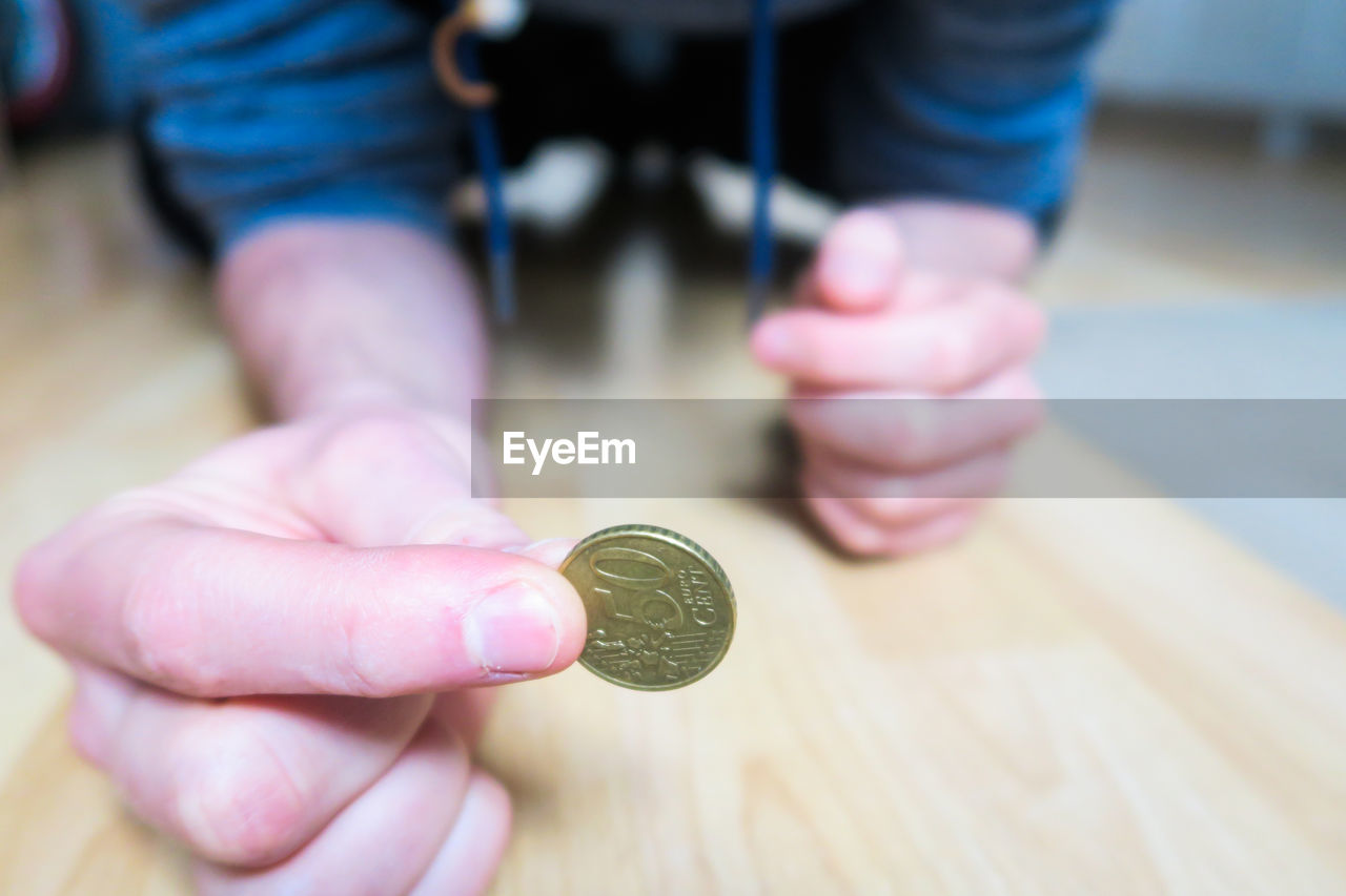 finance, currency, coin, holding, human hand, business, one person, hand, wealth, human body part, savings, real people, focus on foreground, economy, close-up, investment, lifestyles, indoors, midsection, finger, making money