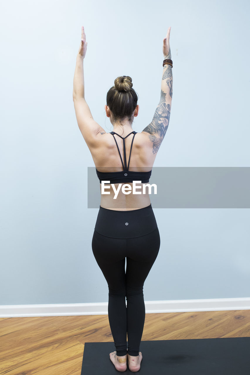 rear view, one person, real people, lifestyles, arms raised, full length, leisure activity, hair bun, sports clothing, indoors, young adult, standing, skill, exercising, young women, day, adult, people