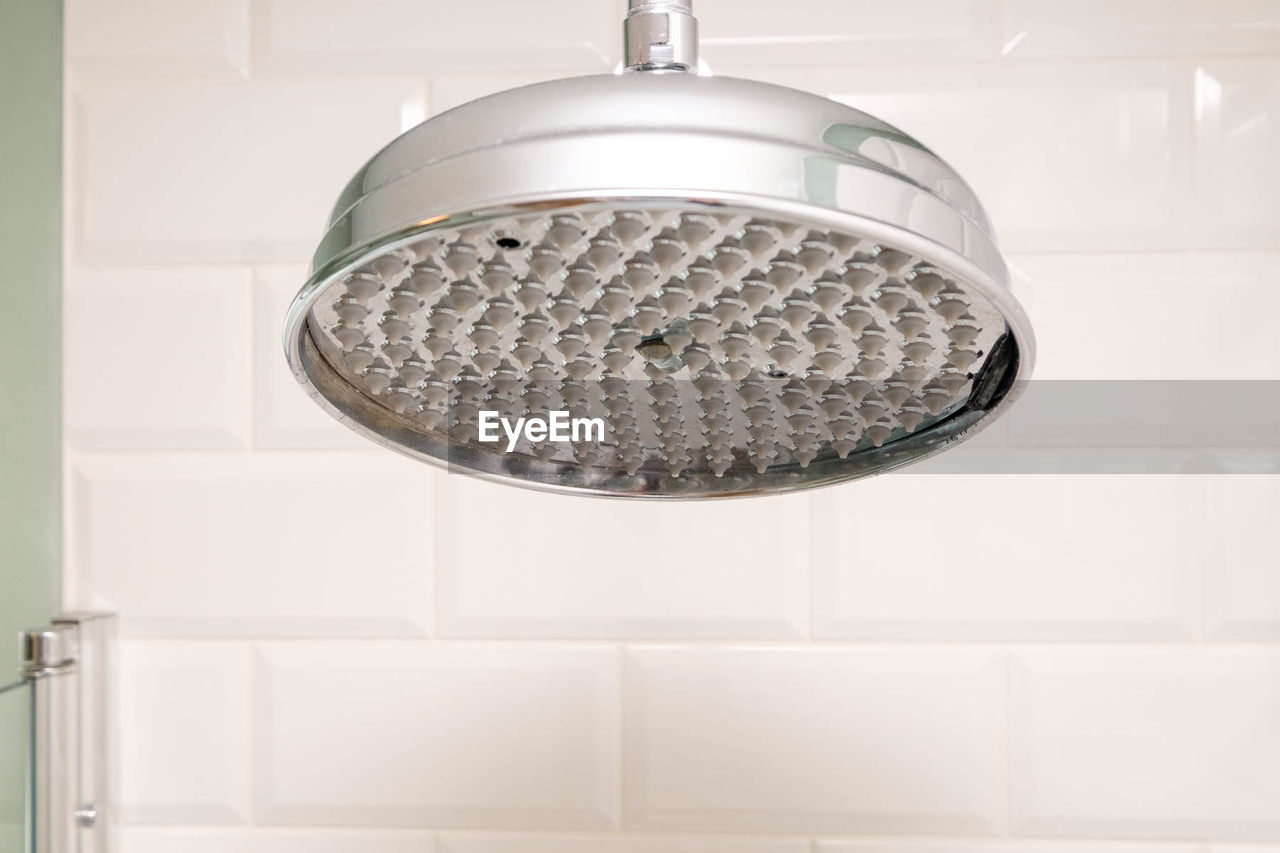 Close-up of shower head in bathroom