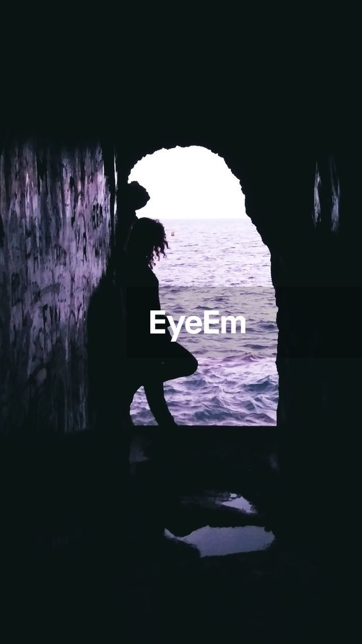 water, silhouette, nature, sea, real people, one person, cave, day, outdoors, leisure activity, standing, arch, beauty in nature, rock - object, rock, full length, men, rock formation, dark
