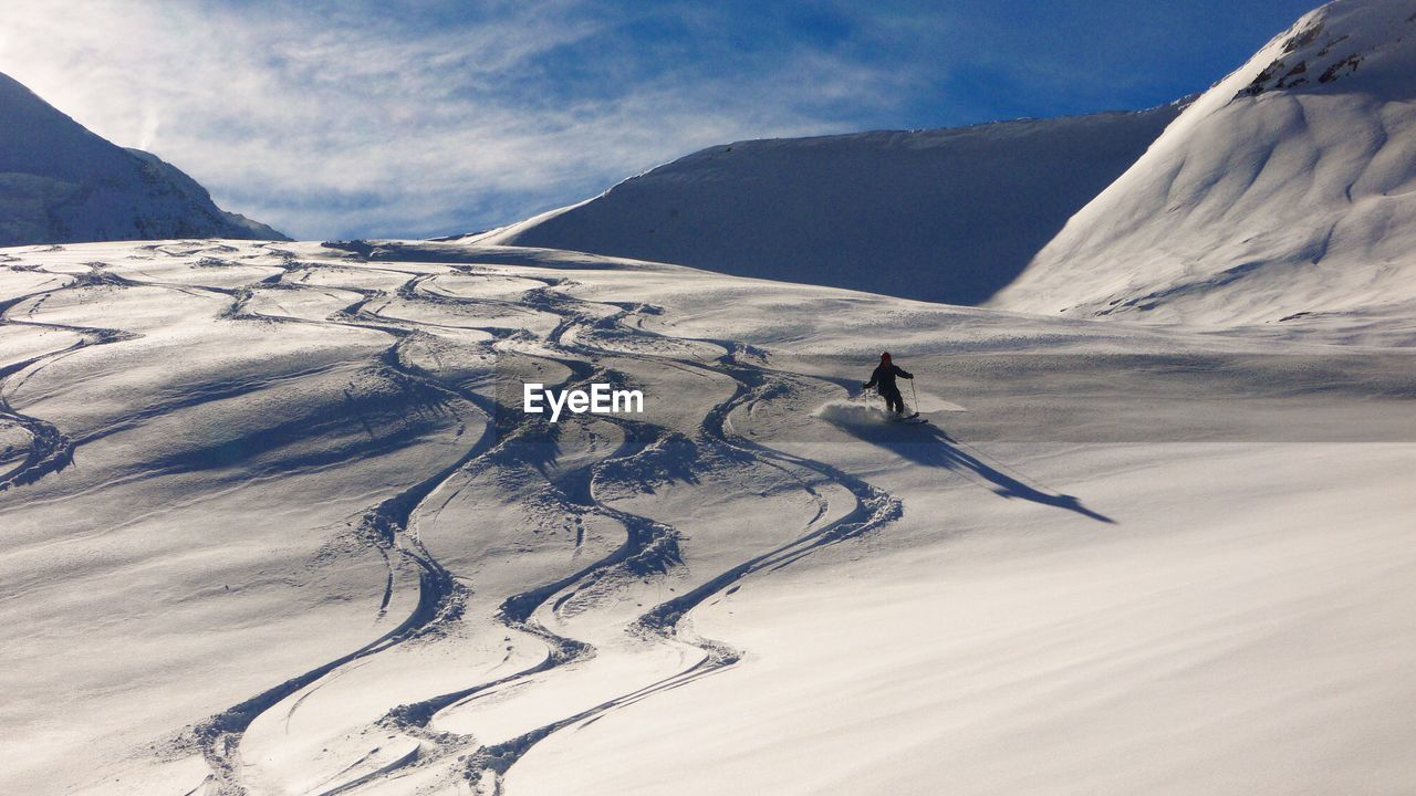 Rear View Of Person Skiing On Snow Covered Mountain Against Blue Sky