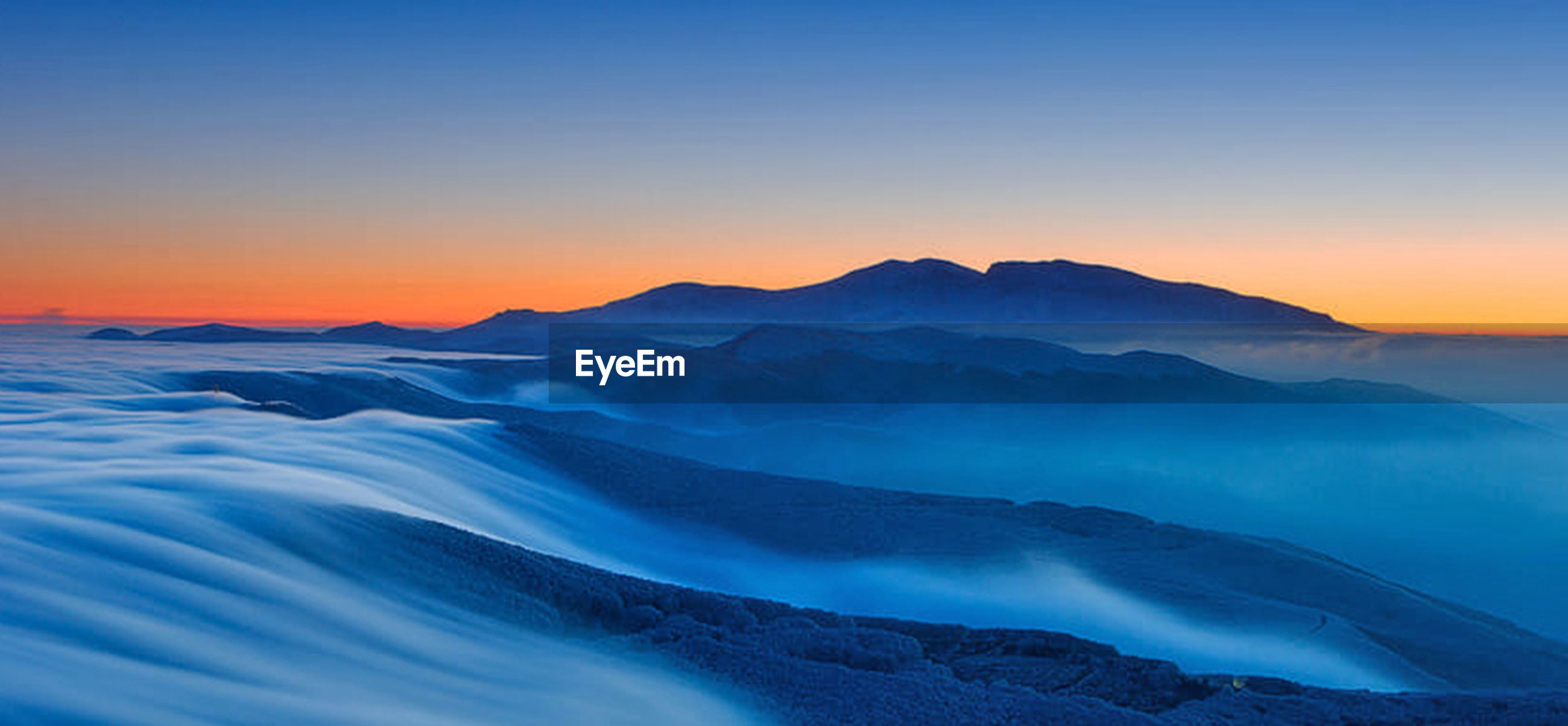 SCENIC VIEW OF MOUNTAINS AGAINST BLUE SKY AT SUNSET