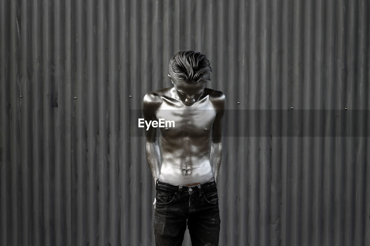 Shirtless Man With Painted Body Standing Against Corrugated Iron