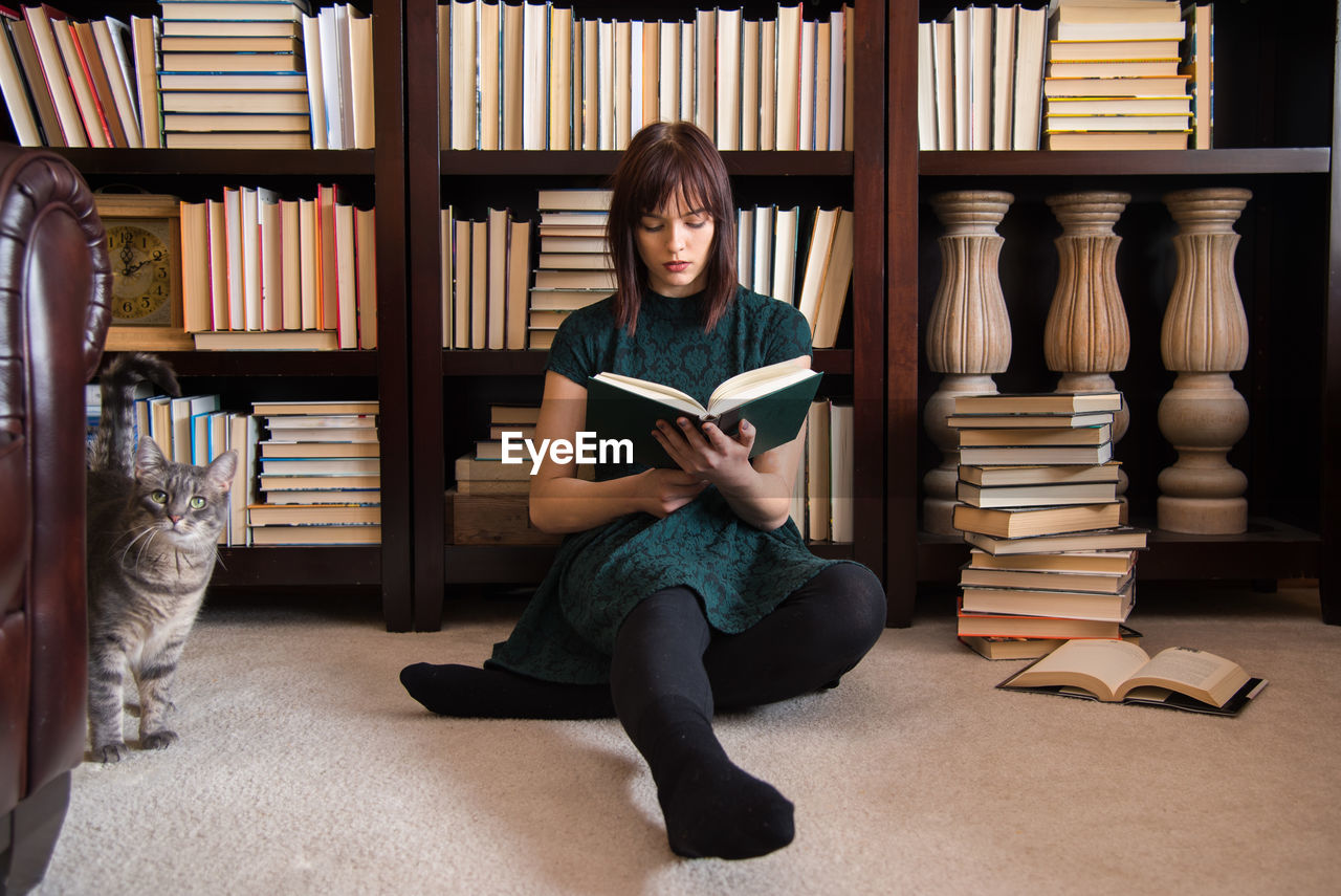 publication, book, shelf, bookshelf, education, sitting, full length, learning, indoors, reading, activity, people, real people, casual clothing, holding, library, front view, leisure activity, literature, studying, hairstyle