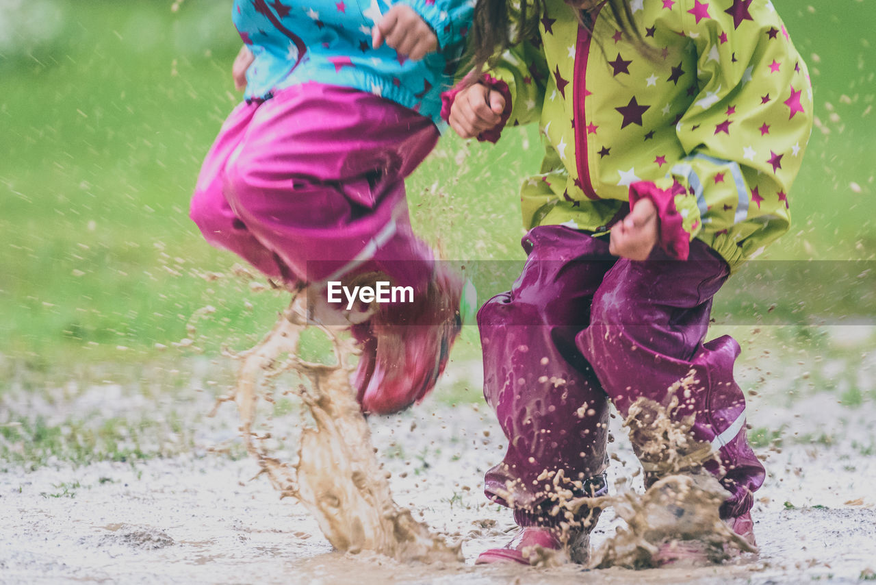 Low Section Of Children Playing In Puddle