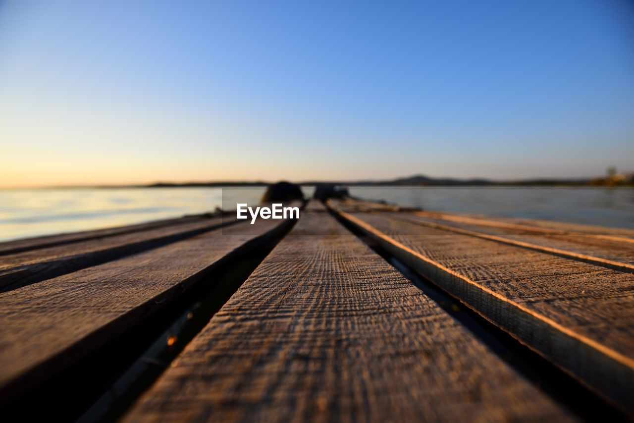 sky, wood - material, water, nature, the way forward, sea, direction, selective focus, clear sky, diminishing perspective, sunset, pier, outdoors, copy space, scenics - nature, unrecognizable person, beauty in nature, one person, leisure activity, surface level, horizon over water